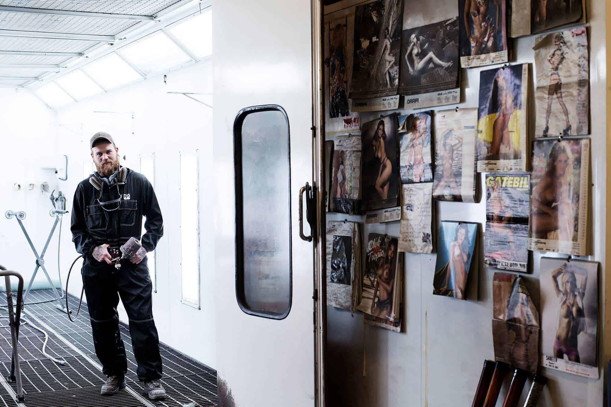 Mann, skjegg og verktøy. I lakkeringshall. Med babes på veggen. Som seg hør og bør, får en vel si. // Foto: Joakim Andreassen